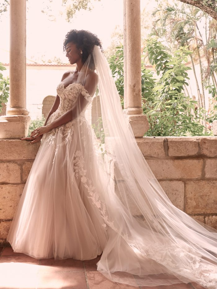 Black Model Wearing Off-the-Shoulder Dreamy Ball Gown Wedding Dress with Bridal Veil Called Orlanda by Maggie Sottero