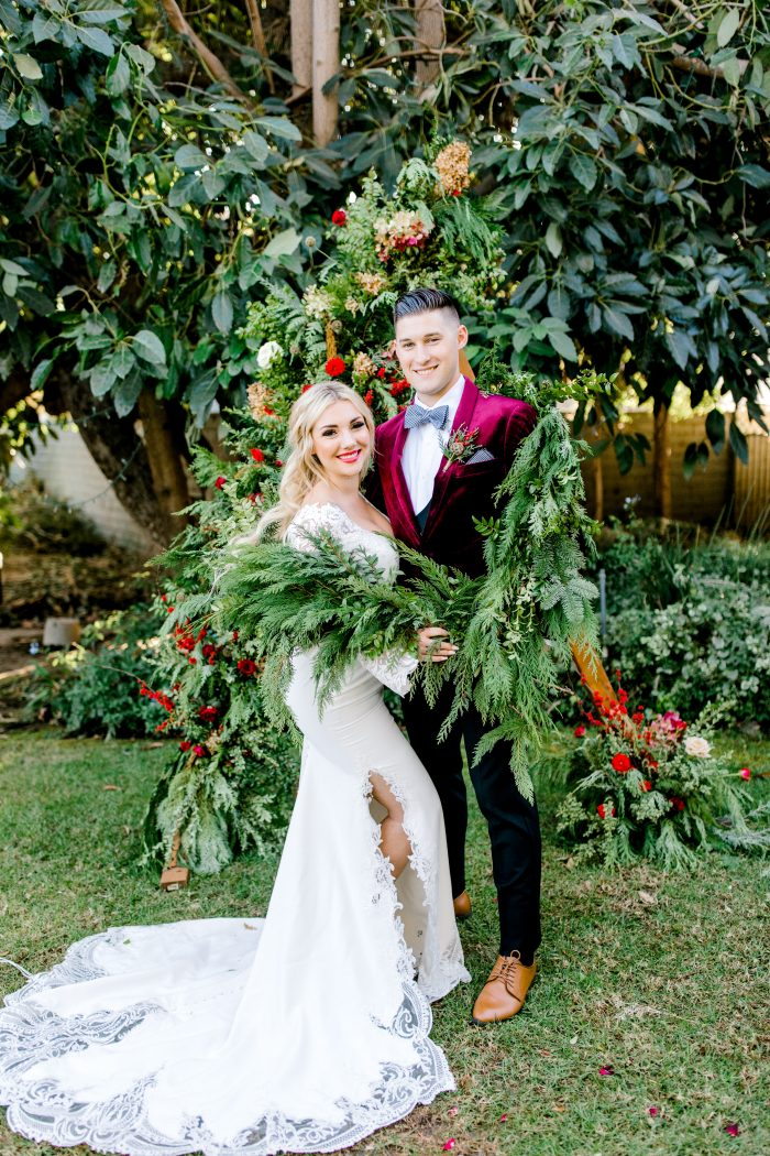 Groom in Velvet Suit with Real Bride Wearing Luxe Crepe Bell Sleeve Wedding Dress Called Armante by Sottero and Midgley
