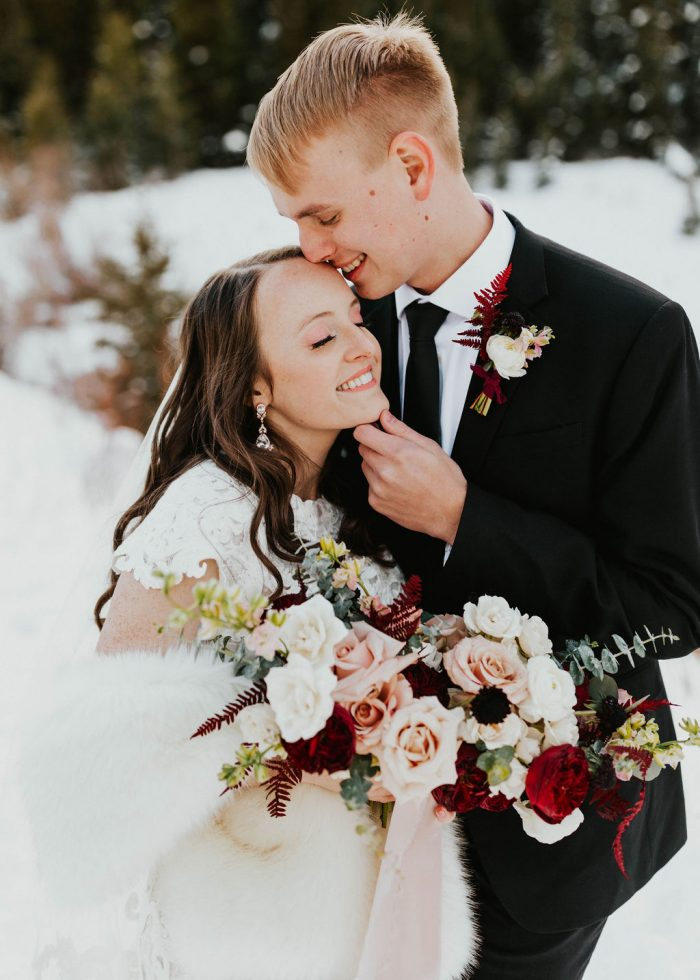Groom in Black Suit Kissing Real Bride Wearing Modest Cap-Sleeve Lace Wedding Dress Called Tuscany Leigh by Maggie Sottero