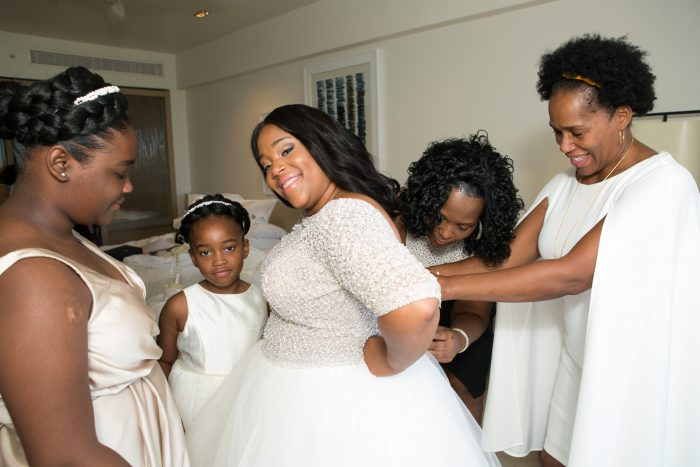 Real Bride wearing Allen Princess wedding dress by Sottero and Midgley getting dressed with her bridesmaids