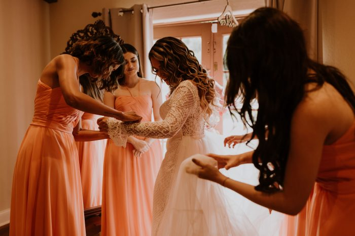 Bridesmaids helping Real Bride wearing Lace Wedding Dress called Antonia by Maggie Sottero get dressed