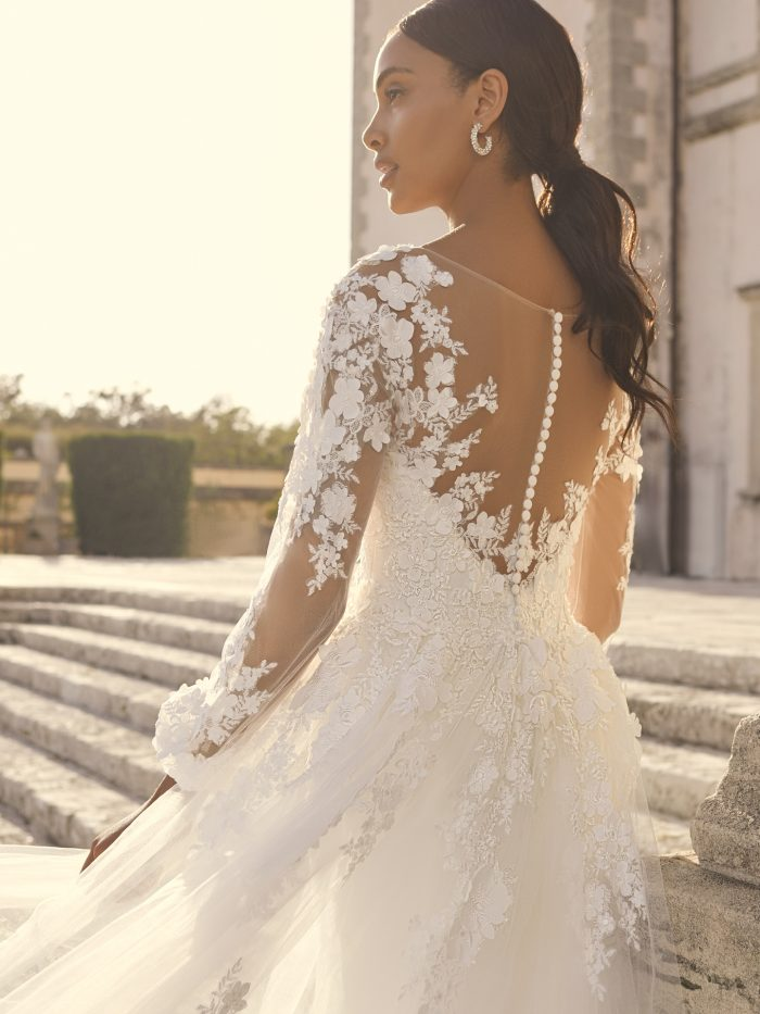Bride Wearing Long Sleeve Crepe Wedding Dress with a Tulle Overskirt Called Arta by Sottero and Midgley