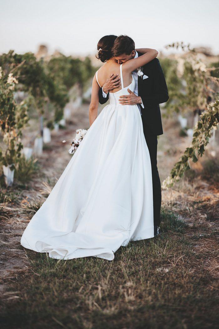 Groom Hugging Bride Wearing Square Back Satin Wedding Dress Called Selena by Maggie Sottero at Vineyard Wedding