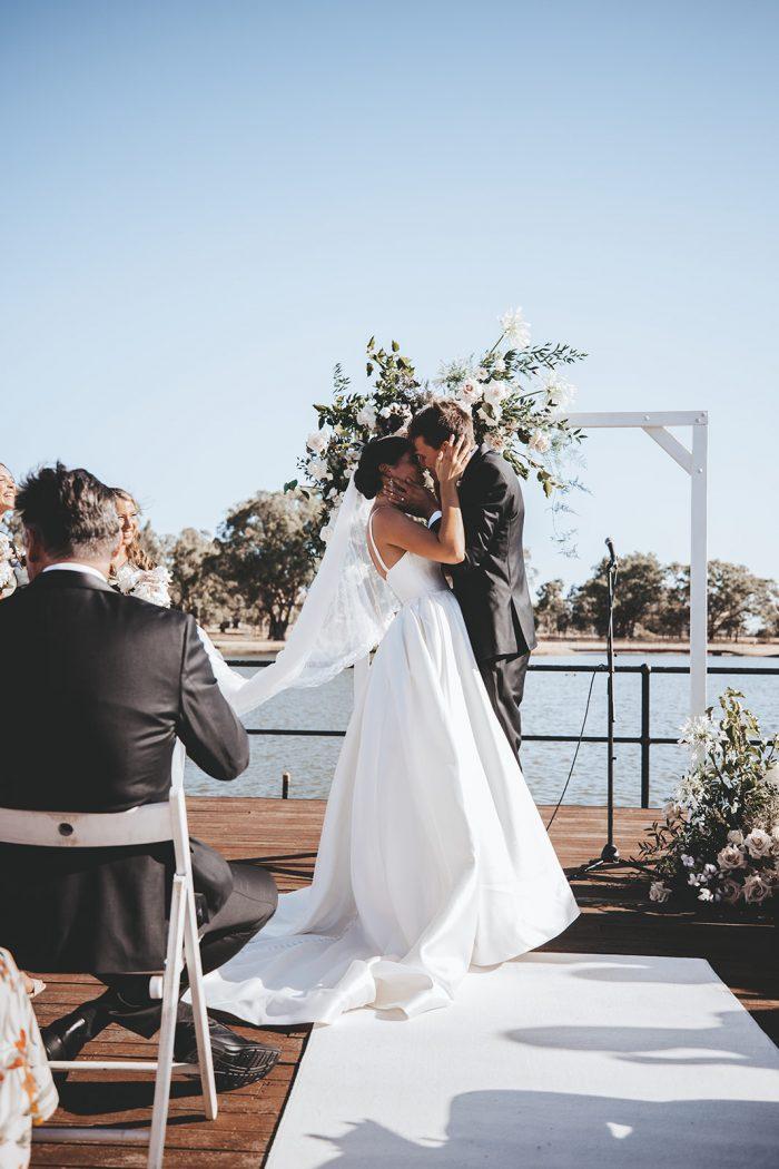 Groom Kissing Bride at Vineyard Wedding Ceremony While Bride Modern Satin Wedding Dress by Maggie Sottero