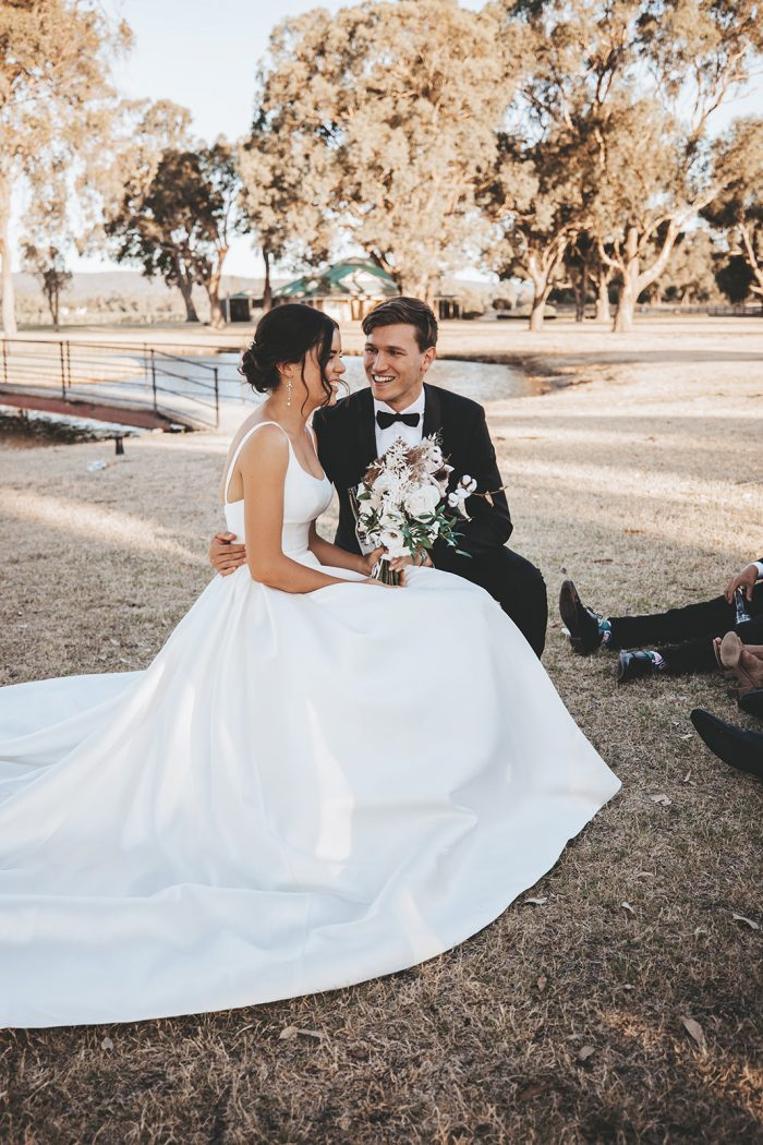 Groom Sitting with Bride Wearing Satin Ball Gown Wedding Dress Called Selena by Maggie Sottero