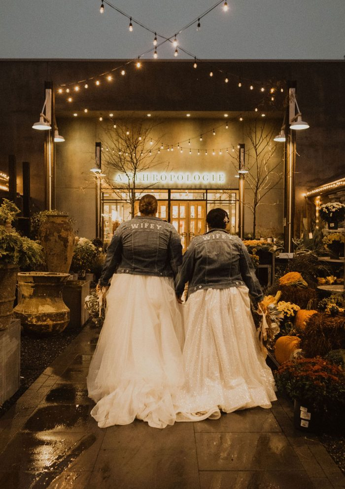 Same-Sex Couple Wearing Matching Denim Jackets That Say Wifey While Wearing Maggie Sottero Wedding Dress