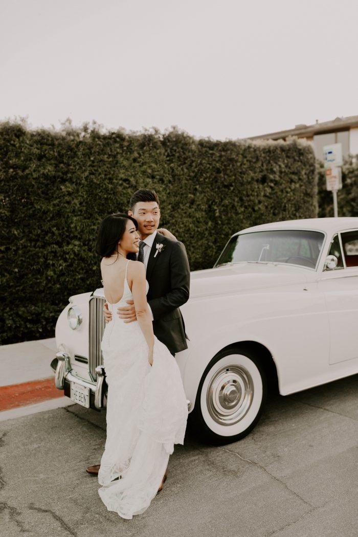 Groom in Front of Vintage Car with Bride Wearing Laidback Wedding Dress Called Elsie by Rebecca Ingram