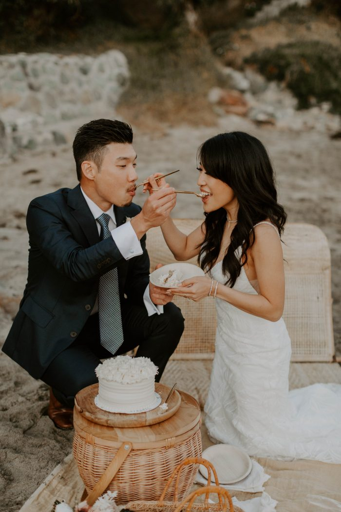 Bride and Groom Eating a White Wedding Cake at Laguna Beach Elopement
