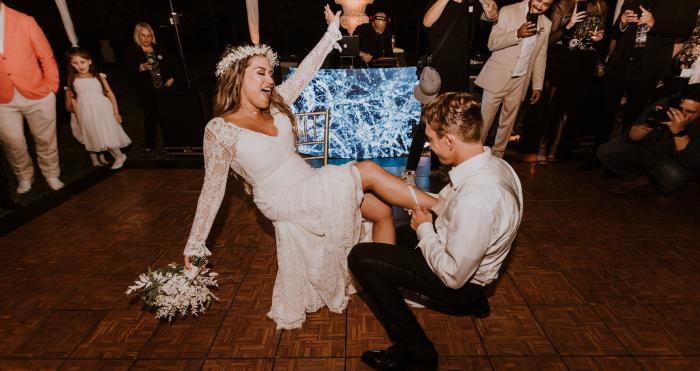Groom Taking Off Bride's Garter During Wedding Garter Tradition Toss