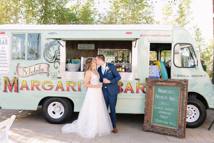 Bride Kissing Groom In Front Of Margarita Bar Wearing Raelynn by Rebecca Ingram
