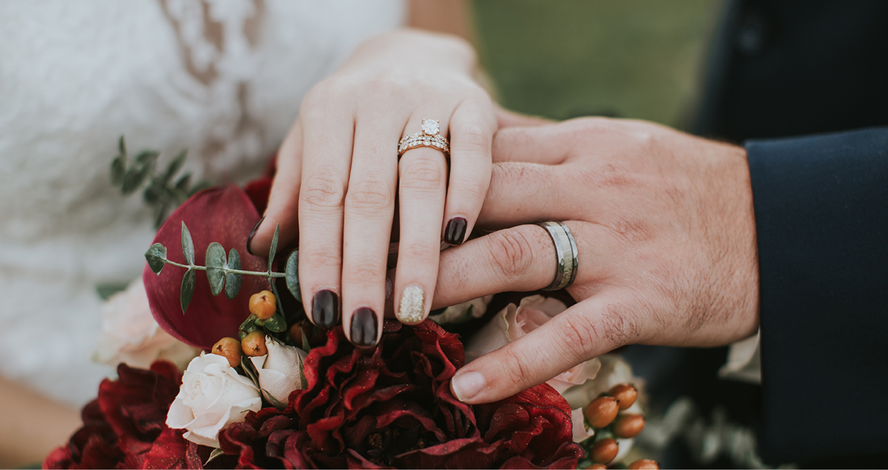 Married Couple Overlapping Hands On Top Of Flower Bouquet Showing Wedding Rings