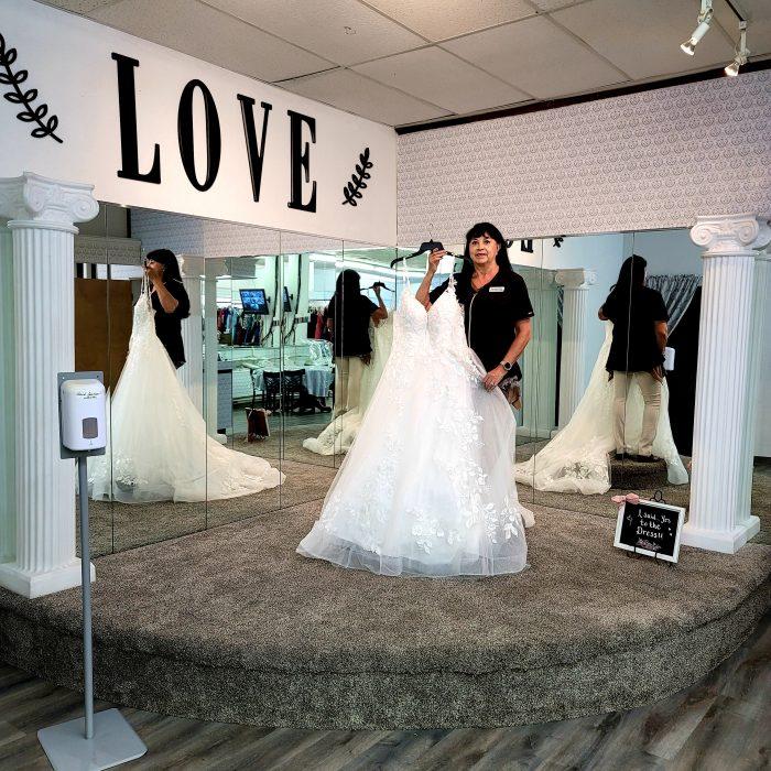 Jae-Geo Bridal and Tuxedo Boutique Owner Holding A Wedding Dress