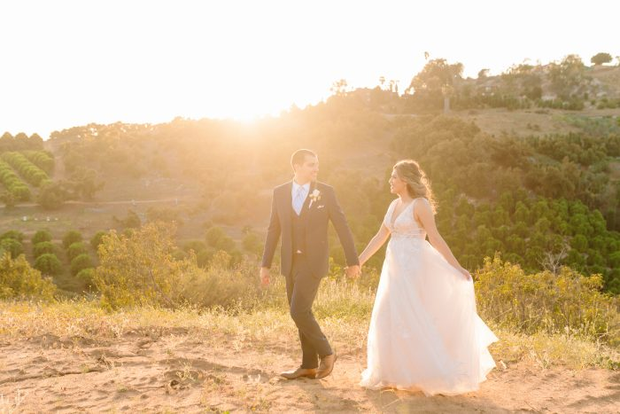 Bride with Groom Holding Hands In Nature Wearing Raelynn Wedding Dress by Rebecca Ingram